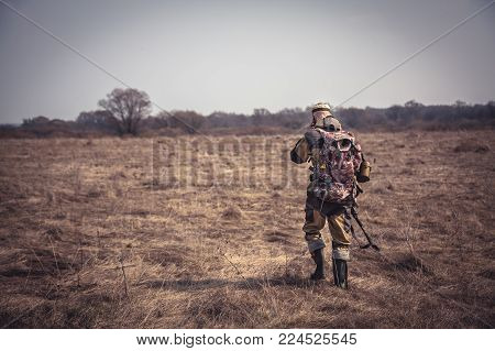 Hunter Man In Camouflage With Shotgun And Backpack Going Through Rural Field During Hunting
