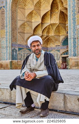 Isfahan, Iran - April 24, 2017: Iranian imam in turban sits in the courtyard of Jame Mosque.