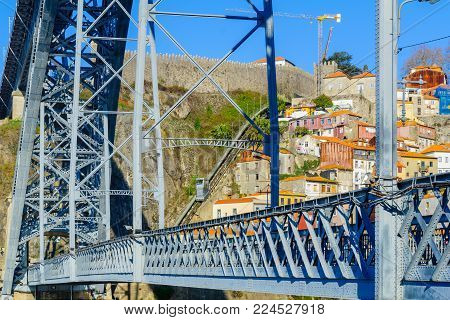 PORTO, PORTUGAL - DECEMBER 24, 2017: View of the Dom Luis I Bridge, and the Funicular dos Guindais, with colorful buildings, locals and visitors, in Porto, Portugal