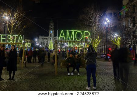 PORTO, PORTUGAL - DECEMBER 24, 2017: Night scene of the Avenida dos Aliados, and the city hall, with multilingual messages, a Christmas tree, locals and visitors, in Porto, Portugal