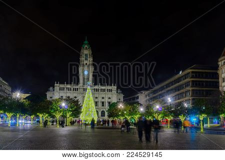 PORTO, PORTUGAL - DECEMBER 24, 2017: Night scene of the Avenida dos Aliados, and the city hall, with a Christmas tree, locals and visitors, in Porto, Portugal