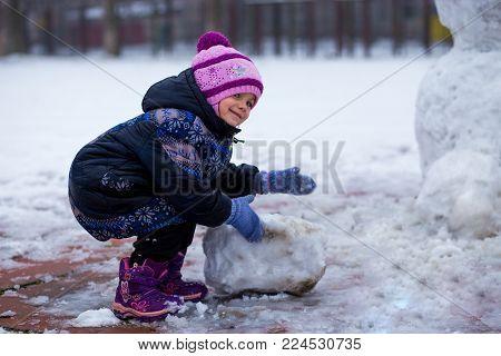A cute little girl walking in snow park, wintertime