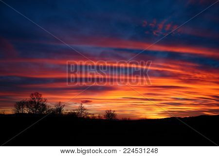 Wonderful colors on a dramatic sunset with red, blue and orange cloud formations