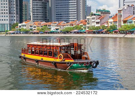 BOAT QUAY, SINGAPORE - AUGUST 18, 2009:  A traditional bumboat (water taxi) at Boat Quay, a historical quay in Singapore, situated upstream from the mouth of the Singapore River on its southern bank.