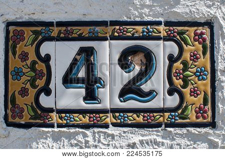 Weathered grunge square faience enameled decorated plate of number of street address with number 42 closeup