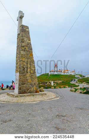 COLARES, PORTUGAL - DECEMBER 28, 2017: View of Cabo (Cape) da Roca, monument and lighthouse, with visitors, Portugal. It is the westernmost point in mainland Europe