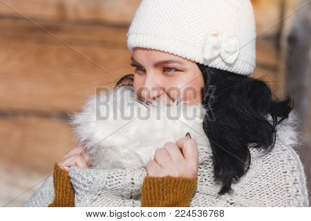 Portrait of a woman hidden behind her scarf. Close up portrait of happy woman wrapped in a scarf with faux fur trim, sunny winter day