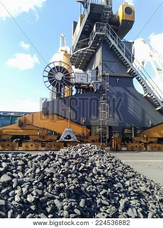 Piles of raw steel briquettes. Heap of coal anthracite in the port. Port cranes for coal loading.