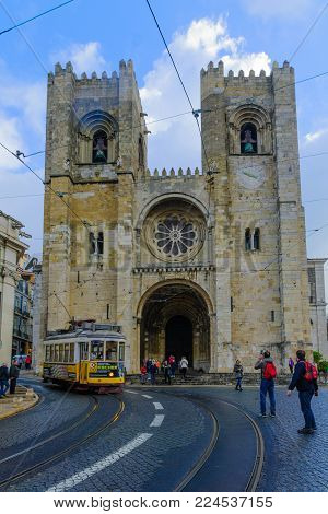 LISBON, PORTUGAL - DECEMBER 29, 2017: View of the Cathedral (Se), with a tram, locals and visitors, in Lisbon, Portugal
