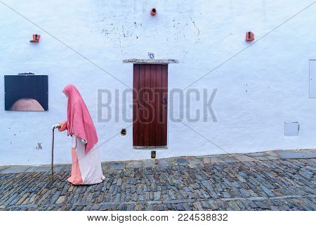 MONSARAZ, PORTUGAL - DECEMBER 30, 2017: Typical house wall and door, and a medieval figure puppet, in the historic village, in Monsaraz, Portugal