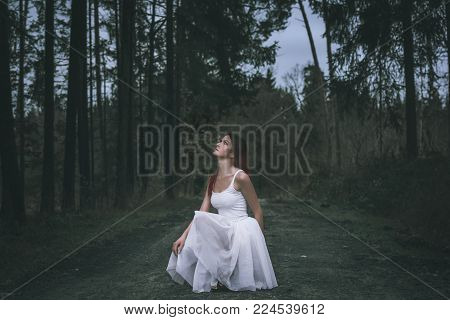 Young woman in tutu skirt looking up - Beautiful woman with an ombre hairstyle, dressed in a white tutu skirt, in a squat position, on a forest road, looking up, in a spring woodland.
