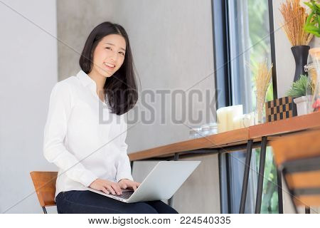 Asian Young Woman Working Online With Laptop And Think Project For Idea At Modern Cafe Shop, Busines