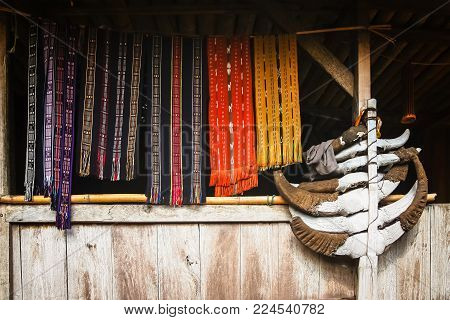 Colorful clothing accessories and scarves hanged to dry on a bamboo stick in the window of the traditional hut in the village Bena on Flores island, Indonesia - UNESCO Heritage list