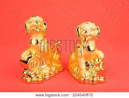 Chinese new year decoration:golden dog statue and gold ingots,Chinese calligraphy Translation:good bless for money poster