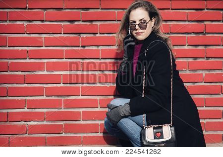Unique stylish and classy young lady using her phone outdoors, sitting next to a red brick wall