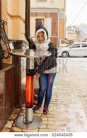 young girl warms up near modern heated table on the street in winter