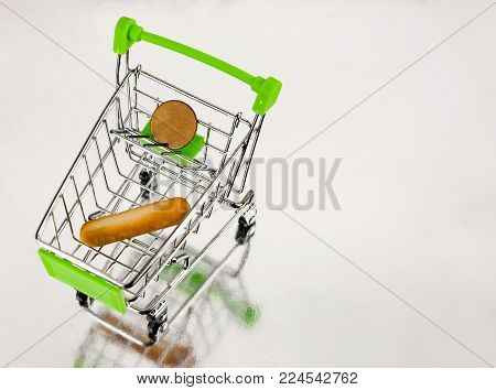 A supermarket trolley with a loaf of bread and a coin