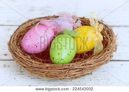 Colorful Easter eggs in a nest displayed on white wooden table