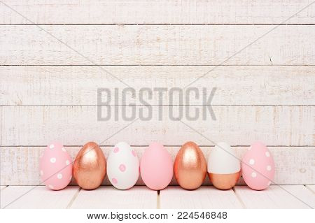 Row of Easter eggs on a white wood background. Rose gold, soft pink and white colors.