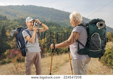 Elderly male hiker taking a picture of an elderly female hiker outdoors