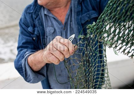 Hands of commercial fisherman repairing his net.