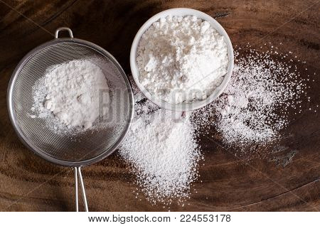 Wheat flour in a bowl and sieve on wooden background prepare for bakery cooking, top view