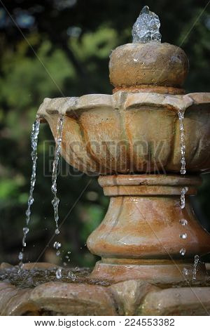 Close-up of water dripping from the bowl of a classic ornamental garden fountain that creates a water feature in a peaceful setting.