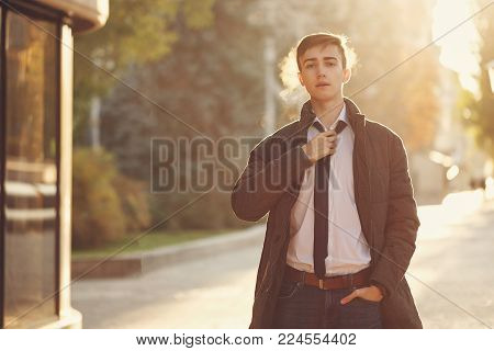 Young stylish teenager guy straightens his tie. Street youth fashion. Backlight of the setting sun