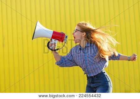 Young attractive girl activist in shirt yelling into loudspeaker. A single picket. Active life position. The struggle for women's rights