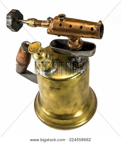 Old fashioned brass blow torch with wooden handle and bronze nozzle