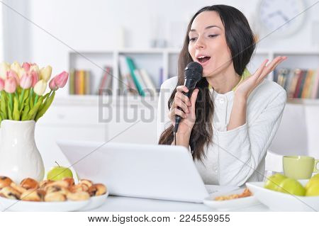 Portrait of beautiful young woman singing karaoke