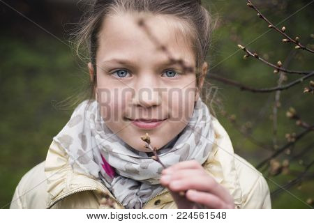 girl breathes in smell of fresh tree buds by early springtime