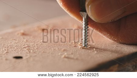 Craftsman drives the screw into the wooden board