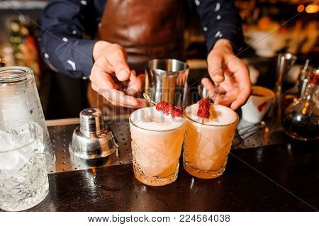 barman in a blue shirt and brown apron prepared two alcoholic cocktails Sour-mix of amber color, decorated with cherries and ice, and put them on the bar counter