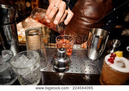 barman in a brown apron is pouring out of a shaker into a crystal glass an alcoholic cocktail of amber color, against a bar counter, glasses with ice and ready-made cocktails