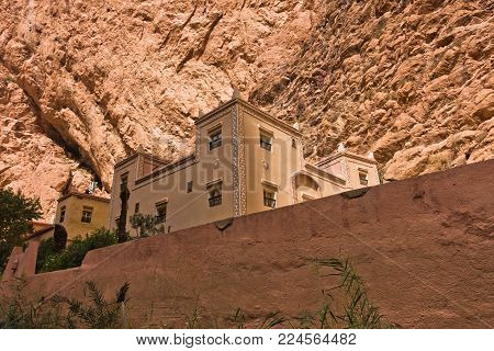 Building in casbah style below giant cliff at Todra Gorge in Morocco, Africa