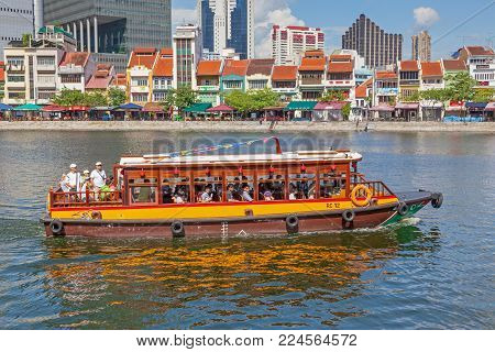 BOAT QUAY, SINGAPORE - AUGUST 18, 2009: A traditional bumboat (water taxi) at Boat Quay, a historical quay in Singapore, situated upstream from the mouth of the Singapore River on its southern bank. The city's financial district is situated in the backgr