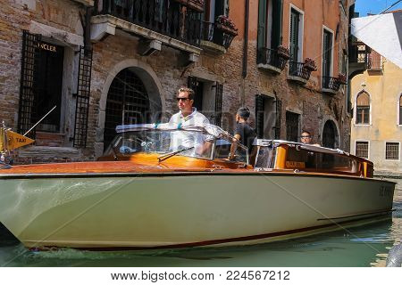 Venice, Italy - August 13, 2016: People in taxi boat on famous Venetian canal