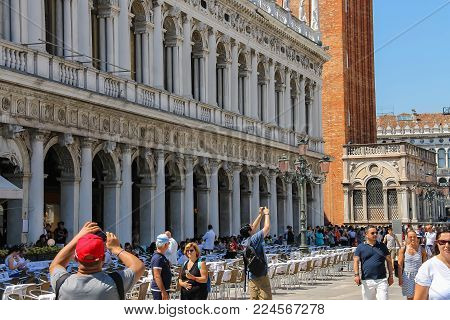 Venice, Italy - August 13, 2016: Tourists walking on famous St. Mark's Square near St. Mark's Campanile (Bell Tower)