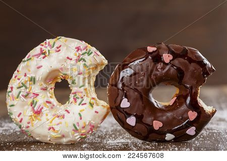 Two bitten donuts with glaze and chocolate on a dark wooden surface close up. American National Donut Day.