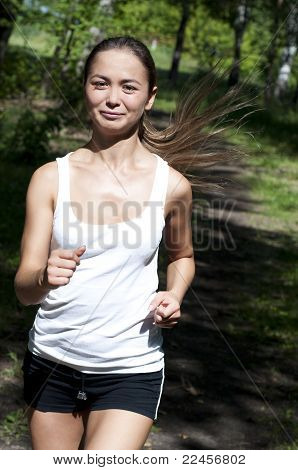 Young Woman Jogging In The Park In Summer