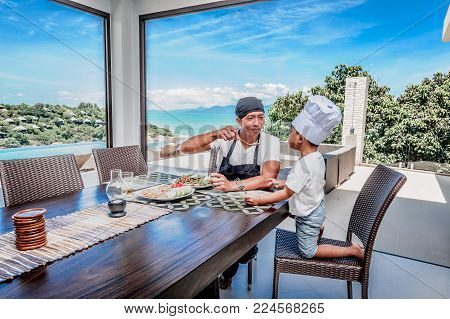 Thai man and his cute son having lunch at home. Playing game of cooks: apron, chef's hat and thai food. Stunning seaview luxury villa. Vibrant color concept