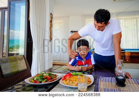 Thai Man And His Cute Son Having Lunch At Home.