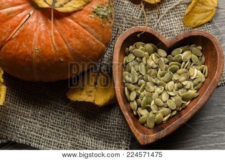 Pumpkin seeds in a wooden bowl with fresh pumpkin and autumn leaves