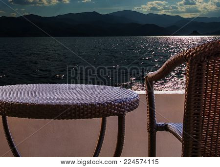 rattan chair set on balcony hotel room with sea and sky view