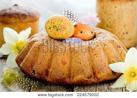 Russian Easter bread kulich paska decorated with painted colorful Easter eggs on Easter dinner table with spring flowers