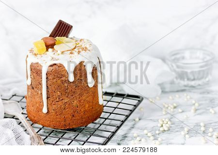 Chocolate paska easter bread with white icing, candied fruits and nuts