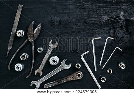 Copy space of working tools on a black wooden surface. Nippers, wrench keys, pliers, screwdriver. Top view. Still life. Flat lay