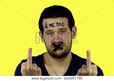 Young man with black adhesive tape on his mouth and inscription `me too` on his forehead in front of yellow background.The man has sealed mouth and he has raised middle fingers.