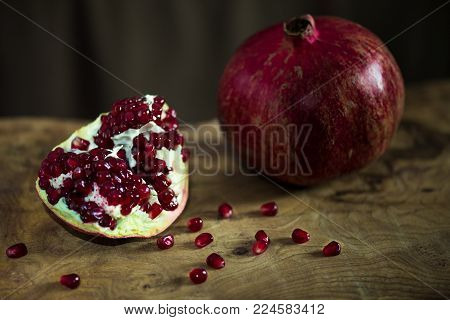 A pomegranate on a wooden table with a  morsel nearby
